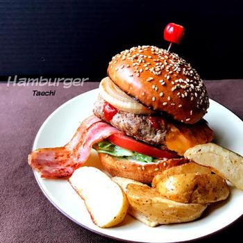 ハンバーグ、ベーコン、オニオンソテーなどを積み上げたデラックスハンバーガー。ベーコンを長いままはさんだりするのもおしゃれですね。おなかも心も満たされるごちそうバーガーです。