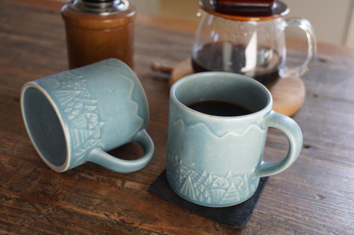 森と山をグルリとあしらった、北欧テイストのマグカップ。大・小の鉄点や釉薬の陰影が味わいになって、表情豊かな仕上がりに。手仕事ならではの風合いが楽しめるのも、よしざわ窯の大きな魅力です。