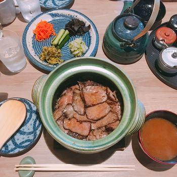 続いて、香ばしい香りと共に、メインの「豊後牛まぶし」が運ばれて来ます。 こちらは、注文が入ってから土鍋で約10分じっくりと炊き上げます。お米は、湯布院産ヒトメボレを使用。ご飯が見えない程、豊後牛サーロインが敷き詰められています。  炭火であぶられたサーロインは、まずはそのまま、次に湯布院産の柚子ごしょうや薬味をのせて、〆には、ダシを注いでお茶漬け風に頂くのがおすすめの食べ方です。