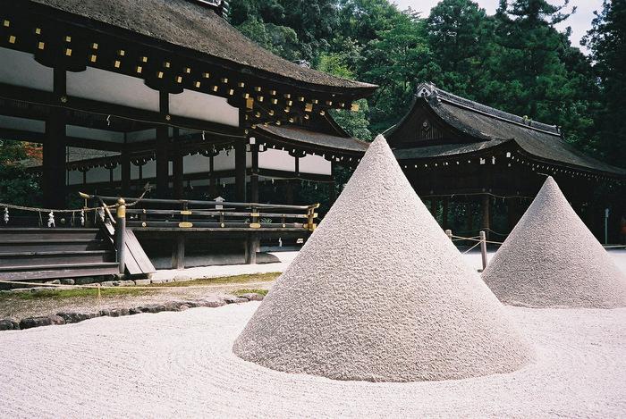 """『上賀茂神社』と言えば、この「立砂(たてずな)」です。本殿の背後にある""""神山(こうやま)""""を形を模したもので、お清めの塩をまいたり、鬼門や裏鬼門に盛り塩をする風習の起源と言われています。京都中心部からは離れていますが、強力なパワーに引き寄せられてか、下鴨神社同様にいつも多くの参拝客で賑わっています。"""