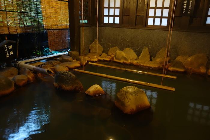 こちらは温泉街にあり、創業三百年の歴史を誇る「黒川温泉 御客屋」。多彩な湯船のひとつ「里の湯」は2本の竹につかまり、深い湯船に立って入る「立ち湯」です。
