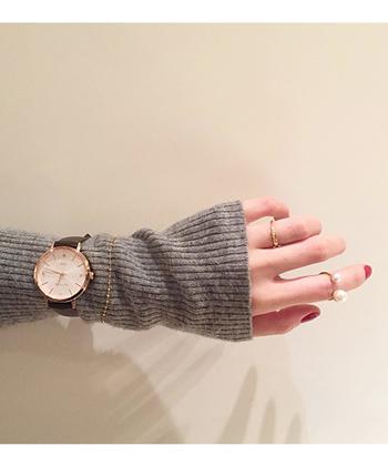 シンプルなグレーニットの時は、シルバーだと埋もれてしまいます。ゴールド系の腕時計やブレスレットをニットの上から巻くことで、手首に女性らしい華やかさをプラスできます。