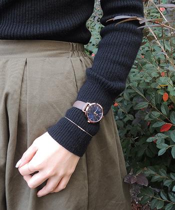 黒のリブニット×カーキフレアスカートには、落ち着いたブラウンベースの腕時計をニットの上から巻いてみましょう。シンプルなブレスレットとの重ね付けも素敵です。