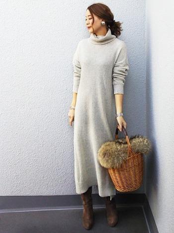 淡いライトグレーのニットワンピースに、くすみ感のある茶系のロングブーツを合わせたコーディネート。ファー付きカゴバッグが季節感を添えています。