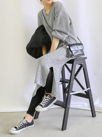 グレーワンピースのレイヤードスタイルの定番といえば、黒のレギンス。サイドスリット入りのロング丈ワンピースの裾から覗かせて、ほんのり女性らしさを演出しています。