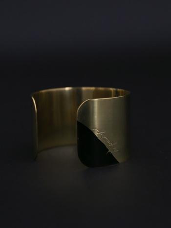 真鍮素材の幅広なブレスレット。アクセントに黒のアクリルペイントが効いています。ゴールドやシルバーといった輝きにはないプリミティブでモダンな印象のこちらは、個性的なスタイリングがお好きな大人の女性におすすめです。