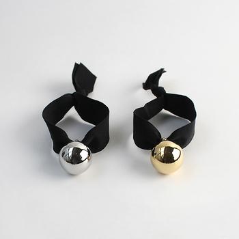 ヘアゴムとしても2WAYで使えるプティローブノアーのブレスレット。太めの黒いリボンにシルバー、またはゴールドのボールモチーフがひとつ。個性的なデザインですが、コーディネートのアクセントになり、意外とお洋服を選ばないのがポイント。