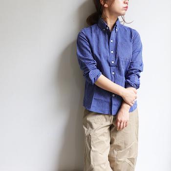 鮮やかな青のストライプシャツには、ベージュのチノパンを合わせて爽やかに。