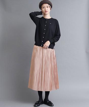 光沢のある女性らしいベージュ系のプリーツスカートは、ベレー帽やカーディガン、ローファーなどを合わせて大人なスクールガール風にまとめてみて。子どもっぽくならないのは、全てシックな黒でそろえたから。