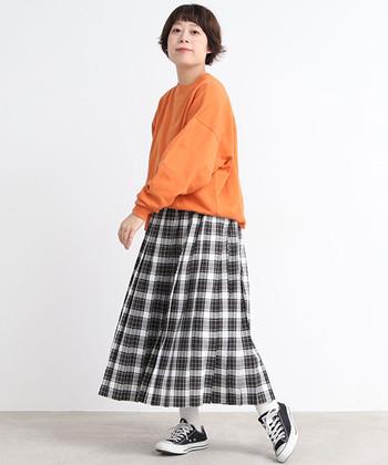 見ているこちらまで温かい気分になれそうな、お日様オレンジ。そんなスウェットには、ピクニックのレジャーシートのようにレトロ可愛い世界観のチェック柄プリーツスカートがお似合いです。