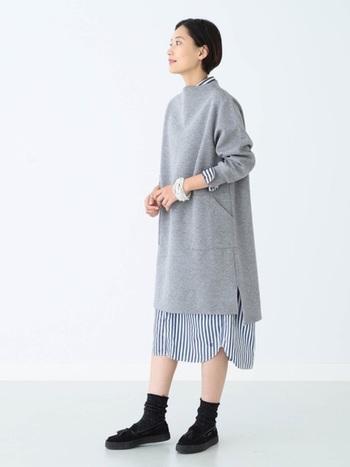 グレーのミドル丈ワンピース×ストライプ柄のシャツワンピースのダブルレイヤードスタイル。このように同じアイテム同士を重ねる時は、ゆったりとした身幅と丈感がポイント!袖口や裾から覗かせる着こなしのバランスが絶妙です。