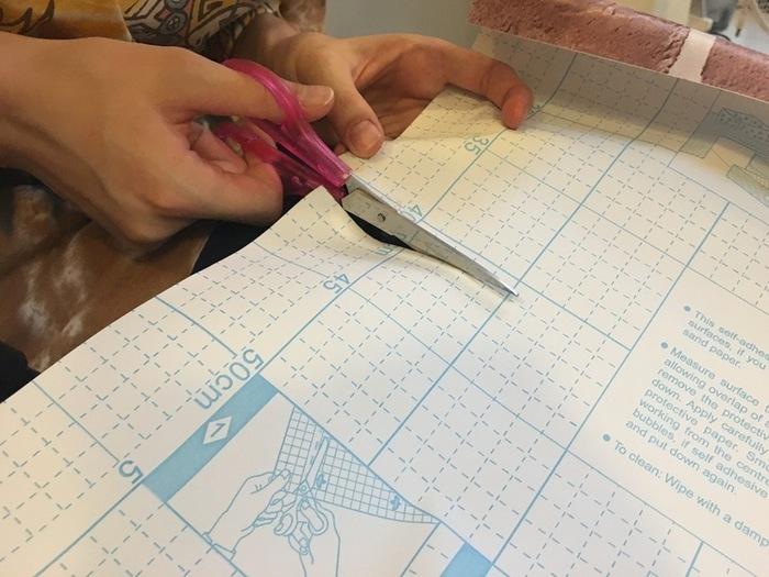 食器棚の貼りたい面に足りるようにリメイクシートを用意したら、それぞれの面のサイズを計測し、カットしていきます。ポイントは少し大きめにカットすること。貼ってから余った部分をカッターで切り取っていきます。