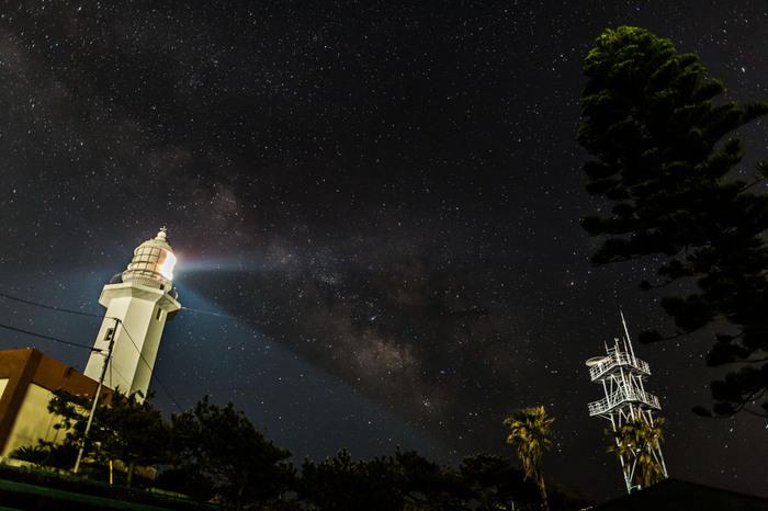 """房総半島の最南端に建つ「野島埼灯台」は、1866年にアメリカ、イギリス、フランス、オランダの4ヶ国条約により、設けられた日本初の洋式8灯台のひとつつです。現在の灯台は1925年に再建されたもので、白く輝く姿から""""白鳥の灯台""""とも呼ばれています。灯台のまわりは遊歩道になっていて、夜の海を照らす灯台の光に負けないぐらい、一面に輝く星空を見ることができます。"""