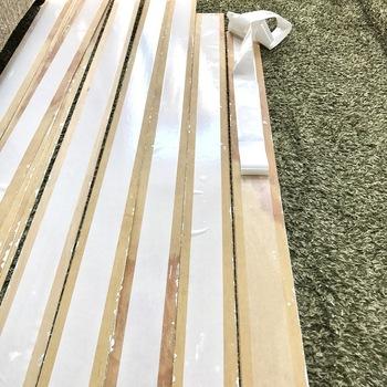 安価な野地板やベニアをペイントして使ってもOK。  壁に釘で設置するのではなく、後に剥がしやすい両面テープで貼り付けていくだけなので簡単に取り付けられますよ。
