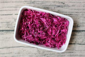 紫キャベツを切って市販のすし酢に漬けるだけで手軽に作れる時短レシピ。紫キャベツは甘酢に漬けておくとより色がきれいに出るうえに、嬉しいことに一週間日保ちしてくれるので、お弁当の彩りにピッタリ。