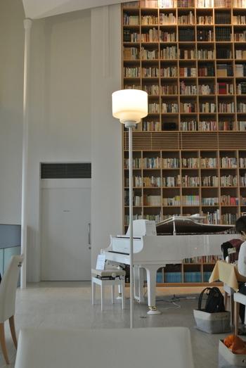 見上げるほどの壁一面にしつらえられた書棚と、純白のグランドピアノが調和する空間。自動演奏の調べが流れる中で、書棚の本は自由に読むことができます。