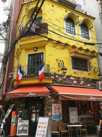 難波の裏通りに佇む黄色い壁がひと際目立つレトロでクラシックな洋館『クレープリー・アルション』。 フランス本場の味を伝えたいという想いから誕生したこちらは、その美味しさに魅かれ連日満席の人気店です。イートインだけでなく、店舗入り口横の赤い小窓から注文すればテイクアウトすることもできます。