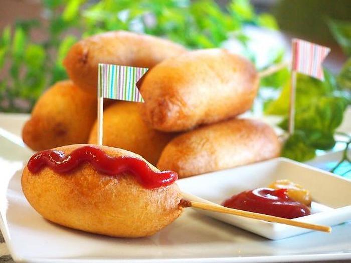子どもにも大人気のアメリカンドッグは、ホットケーキミックスを使って案外簡単に作ることができます。綺麗な形に作るコツは、生地をソーセージにしっかりとまとわせること。そして生地が絡んだらすぐに油に入れて揚げることです。ぜひお試しを!