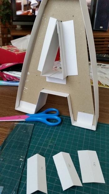 パーツができあがったら組み立てていきましょう。固定する紙を厚紙で作成し、両面テープで取り付けます。裏面は見栄えが悪くなっても大丈夫なので、しっかりと固定しましょう。