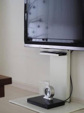 壁掛け風のテレビボードのマグネットを利用して、マグネット式の収納ラックを設置。色味・シンプルさが合わさって、まるで元々セットだったかのようなスッキリとした印象に。