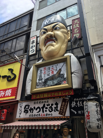 昭和4年創業の老舗で、大阪や海外にも店舗を持つ大阪屈指の大手串カツチェーン店『串かつだるま』。入口にはオーナーの大きい人形が飾られていて、その大きさに圧倒されてしまいそうです。
