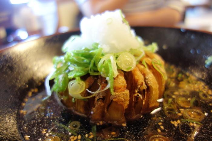 人気NO.1メニューの「タマネギつけ麺」。かつおやさばなどの風味豊かなだしの中には、大きな玉ねぎが丸ごと1個。じっくり低温で揚げているから、玉ねぎの甘みが凝縮され美味。花がパッと咲いたように見える見た目も写真映えしますね。