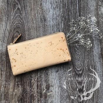 型押しされたカスミソウの総柄デザインが、ナチュラル派さんの心をわしづかみ♪スリムなL字型のファスナー本ヌメ革の財布は、使い込んでいくうちにレザーがいい色合いに変化していくのもまた、魅力的です。