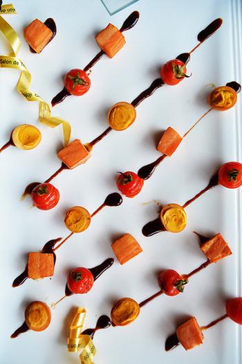 バルサミコを細くたらしたお皿に、ベーコン・トマト・うずら卵の燻製を等間隔に置いて。まるで串に刺してあるかのような楽しいデザインですね。
