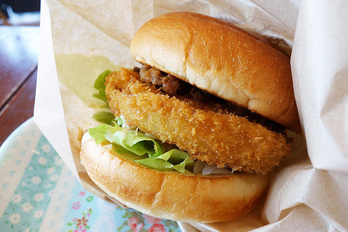 こちらが、2013年に行われた第3回全国ご当地バーガーグランプリで1位に輝いた「あわじ島オニオンビーフバーガー」です。存在感ある厚さ約8mmの淡路島産玉ねぎカツの上には、甘辛く炊いた淡路牛が。淡路島の特産品がギュッと詰まったハンバーガーです。