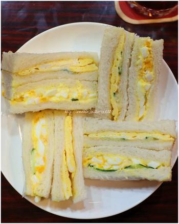 """サンドイッチは、オーダーを受けてから作る玉子焼きとゆで卵のマヨネーズ和え、キュウリが入ったオリジナル。ふわふわの中にしっかり食感を感じられるペリカンのパンとの相性抜群。 """"喫茶店の軽食=サンドイッチ""""というイメージを裏切らない味です。"""