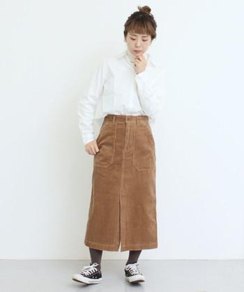 クリーンな真っ白シャツで、重たいイメージになりがちな厚手ボトムを軽やかに着こなして。ちらっと見えるタイツは、スカートのキャメルと好相性なブラウンをセレクト。