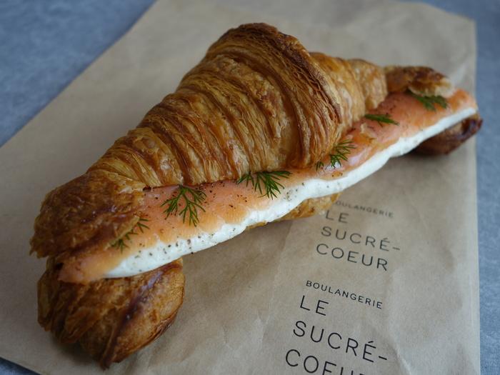 ル・シュクレクールの看板メニュー「クロワッサン」。ランチには、スモークサーモンなどをサンドしたものが人気です。センスのいい紙袋に入れてくれるのも気分があがります。