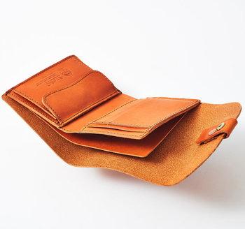 ●コンパクト財布  半円のフラップが特徴のレザーウォレット。丸みを帯びたデザインは持った際にしっくりと馴染み、ずっと触っていたくなる手触りも魅力です。中のコインポケットやカードホルダーの部分も表と同じレザーを使って仕上げています。  <仕様> ・お札入れ:2箇所 ・フラップ付きコイン入れ:1箇所 ・カードポケット
