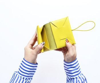●コンパクト財布  折り紙を連想させるデザインで、ステッチを使わないつくりが特徴。なめらかな牛革は使うごとにゆっくりと手に馴染み、表情を変えていきます。ゴムでとめることで中身も落ちず、コンパクトにまとまります。  <仕様> ・お札入れ:1箇所 ・フラップ付きコイン入れ:1箇所 ・カードポケット:1個