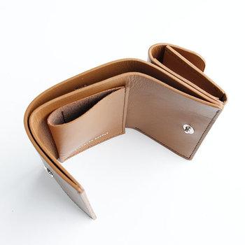 ●コンパクト財布  手のひらサイズに収まるよう、機能は最低限にした三つ折りのコンパクトなお財布。小さいながらも、お札は折りたたまずに収納ができます。全体的にベタ貼りとコバ塗りを多用した、贅沢な作りにも注目です。  <仕様> ・お札入れ:1箇所 ・フラップ付きコイン入れ:1箇所 ・カードポケット:1箇所
