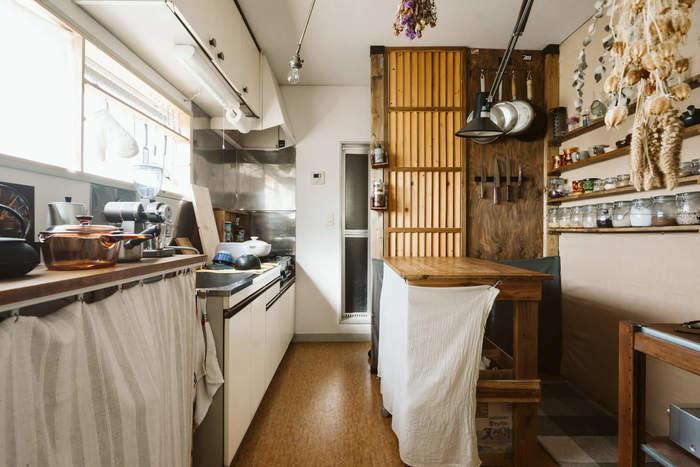 大きく広々とした開放感のあるキッチンです。 注目は壁面ラック。ずらりと並んだレトロなガラス容器には、調味料が。 ペンダントライトやドライフラワーも、カフェ風キッチンにおすすめなアイテムです。
