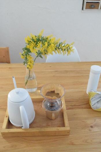 ダイニングテーブルにミモザをひと枝。変に手を加えず、しなりを生かした自然のままの姿がいい感じ。