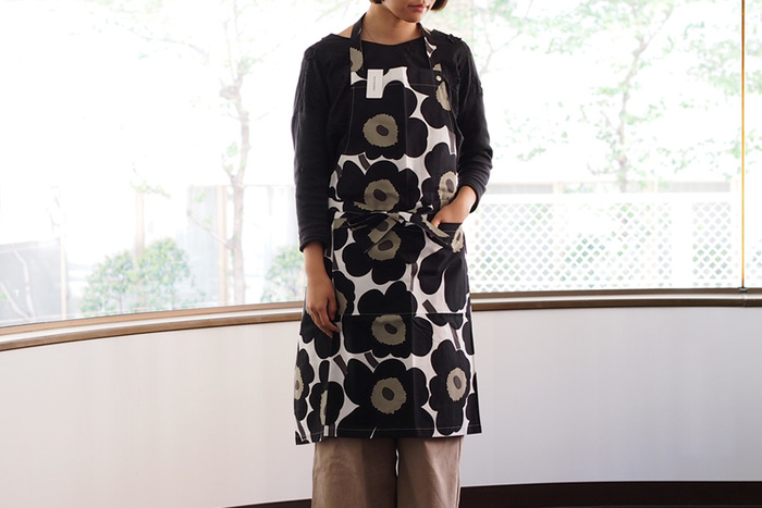 こちらは世界的に有名なデザインハウス、「marimekko(マリメッコ)」のウニッコ柄エプロンです。デザイナー・Maija Isola(マイヤ・イソラ)が1964年にデザインしたPieni-Unikko(ピエニ・ウニッコ)は、ケシの花をモチーフにした大胆な図柄が特徴です。カーテンやファブリックパネルなど様々なアイテムに用いられ、ブランドのアイコンモチーフとして世界中で愛され続けています。