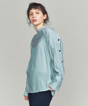 光沢感のある縞模様シャツ。動くたびにキラキラ光のニュアンスが感じられます。袖のボタンもアクセントになって一枚で着るだけで絵になります。