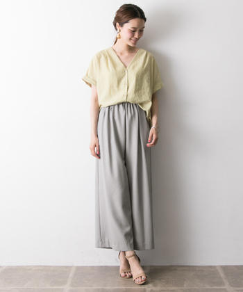 美しいワイドシルエットのグレーパンツには、大人っぽい雰囲気のVネックブラウスが好相性。足元は華奢なサンダルを合わせることで、より女性らしい印象に。全体を淡いトーンでまとめた上品な着こなしは、夏のリラックススタイルにぴったりです。