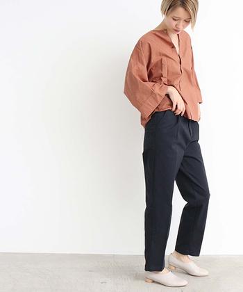 ネイビーのテーパードパンツに、ブラウン系のシャツをゆるくタックインしたコーディネートです。落ち着いた大人っぽいカラーリングで、上品なキレイめコーデが叶います。