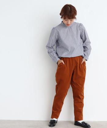 ブラウンのテーパードパンツは、ストライプのブラウスをゆるっとタックインしたスタイリングに。上品な雰囲気のブラウスを、ゆったりシルエットのテーパードパンツで程よくラフに仕上げた着こなしです。