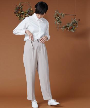 ベルト付きでかっちりした印象のテーパードパンツに、白シャツを合わせたきちんとコーデ。あえて白のスニーカーをチョイスしたカジュアルダウンスタイルは、アウター次第で表情がガラリと変わる着こなしですね。