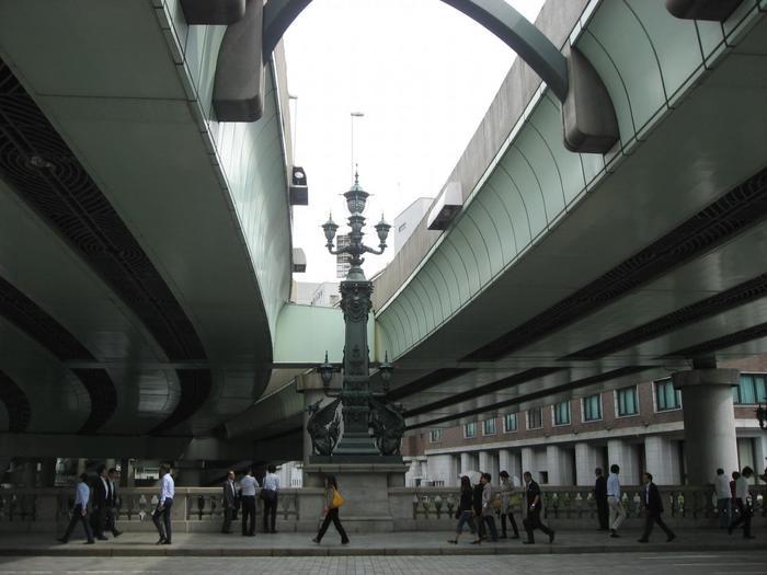 """橋が架かる「日本橋川」は、""""川""""といっても、元々は、人の手によって開削された運河(水路)。かつての江戸は""""水の都""""。江戸中、網目のごとく水路が張り巡らされていました。  【画像中央が「中心柱」。通常は「親柱(先の画像)」よりも低いが、日本の""""道路起点""""となっているため、異例的に高くなっている。道路中央部には「日本国道路元標」のプレートが埋め込まれている。】"""