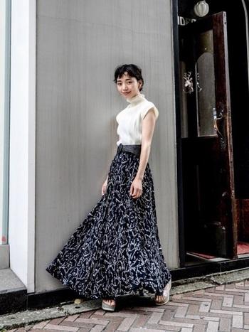 ふわりと風に舞うロングスカートを使った、50年代らしいエレガントなコーディネート。個性的な柄のスカートも、モノトーンでまとめることで落ち着いた印象に。