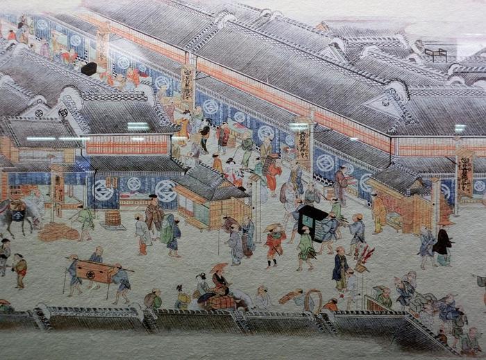 """そして、当地に参集した人々が携えてきた諸国の文化や技術もまた、当地で磨かれ、人々の間で受け継がれていきました。水陸共に交通の要所だった「日本橋」は、""""魚河岸""""の誕生をきっかけにして、江戸の流通、経済の中心として急成長を遂げ、多様な人々が結集するよって文化も大いに発展し、天下の城下町""""江戸""""一番の繁華街として栄えたのです。  【「日本橋」は、絵師が浮世絵で描いている通りに、物と人に溢れた一大商業地。近隣には金座や銀座がおかれたように、金融を含めた経済の中心地として活況を呈し、""""朝は魚河岸、昼は芝居町、夜は吉原""""と言われている通り、遊郭、歌舞伎小屋もあり、文化も成熟していた。魚河岸の大問屋は、豊富な資金力を浮世絵師や俳諧師、浮世絵師らといった江戸文化を担う人々に惜しげなく注ぎ、文化人や学者を身内から多く輩出し、江戸文化を支える大スポンサーとなっていた。  (画像は、『熈代勝覧(きだいしょうらん)』の「三井越後屋の立看板」。江戸随一の呉服商「三井家の越後屋」が描かれている。立看板に「現銀無掛直」とあるように、""""掛売り""""が通例だった当時、""""現金商法""""を打ち出して大当たりした。百貨店の「三越」の名前は、「""""三""""井家の""""越""""後屋」にちなんでいる。】"""