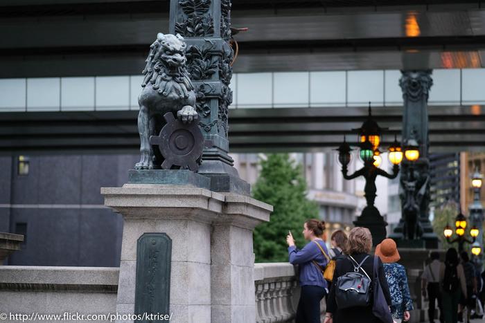 名橋《日本橋》が、日本橋川に初めて架けられたのは、江戸幕府が開かれた慶長8(1603)年のこと。家康による街道整備計画に際して架けられ、五街道の基点となりました。  【現在の国道にかかる石造アーチ橋は、明治44年に架橋された19代目(国の重要文化財に指定)。全体の意匠や装飾を式したのは、横浜赤レンガ倉庫を設計した建築家の妻木頼黄(つまきよりなか)で、和洋の様式を折衷したデザインとなっている。  画像手前の「親柱」唐獅子、橋中央部の「中心柱」の麒麟像の製作は、彫刻家・渡辺長男(わたなべおさお)。親柱の唐獅子が持つのは、東京市の紋章で、獅子の下の銘板に刻まれた「日本橋」の揮毫は、幕府最後の将軍・徳川慶喜による。】