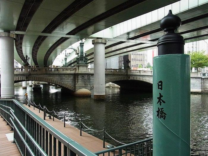 """「日本橋川」は、江戸初期に整備した際に開削した水路の一つで、元々は""""平川""""という川の流れを利用して、人の手によって掘削したものです。  【*ほぼ全流路が首都高速の高架下になっている現在の「日本橋川」は、神田川の派川(分流)。JR水道橋の西側に架かる小石川橋で神田川から分岐し南下、神田橋、日本橋、江戸橋を通過し、永代橋付近で隅田川に合流する。橋袂の「日本橋船着場入口」からは、日本橋や隅田川、神田川や東京湾の周遊クルーズ船が様々に出ている。詳細は記事最後のInformationを参照のこと。】"""