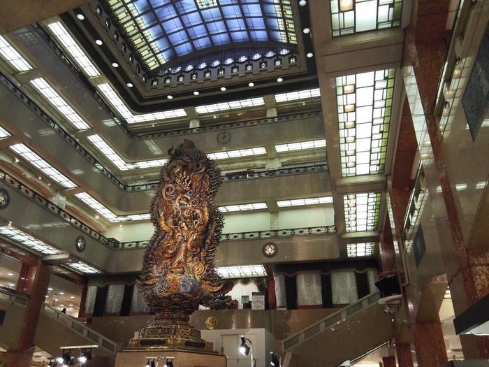 【「三越日本橋本店」では、1階エントランスホール、竣工当時そのままのエレベーターも必見。 中心に「天女像」を据えた5回まで吹き抜けのエントランスホールは、竣工当時は、天井にステンドグラスがはめ込まれ、自然光が内部まで入っていたという。照明器具や柱、細部にまで、大正、昭和初期の流行したアールデコ装飾で統一されている。】
