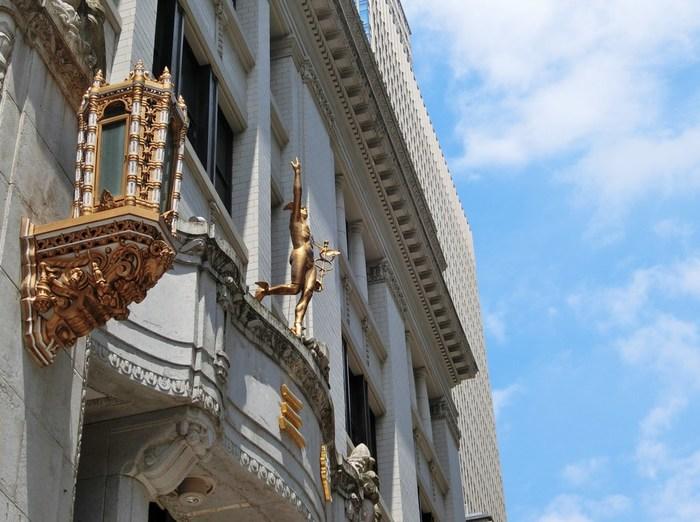 """甚大な被害を受けた関東大震災以後も、道路や河川の改修、拡張が行われ時代が移り変わっても、その勢いが止まることはありませんんでした。  【「三越日本橋本店」の前身は、「三井越後屋」。伊勢松坂から江戸に出た三井高利が、ここ日本橋(駿河町)に店舗を出し、""""店先売""""や""""現金掛け値なし""""等、新商法を次々と打ち出して大成功をおさめ豪商となり、三井財閥の起源となった。  ライオン像と、ルネッサンス風建築で目を引く「日本橋三越本店」は、大正3(1914)年に竣工、昭和初期まで増改築を繰り返し現在に至る。2016年に国の重要文化財指定され、日本橋の名所の一つになっている。(無料の歴史ツアーが開催されている詳細は、記事最後Informationへ)  必見は、外部内部の装飾された彫像や彫刻。""""三越ライオン""""が有名だが、他にも様々な文化的に価値の高い装飾が施されている。特に見逃せないのは、ライオン像のあるエントランス上部外壁。ローマ神話で登場するマーキュリー(富の象徴、商売繁盛をもたらす神様)が立っている。手にしているのは、商いのシンボル「杖」であり、神の遣いである蛇が巻き付いている。】"""